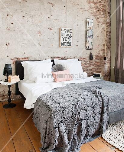 Graue, gehäkelte Tagesdecke auf Doppelbett vor teilweise verputzter Ziegelwand im Schlafzimmer mit Holzdielenboden
