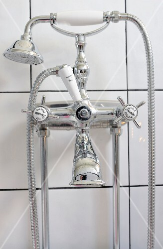 Vintage-style bath taps mounted on white-tiled wall