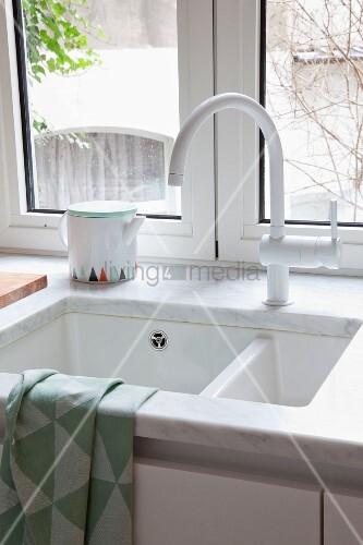 marmor arbeitsplatte mit eingebauter sp le und weisse armatur vor fenster mit ausblick bild. Black Bedroom Furniture Sets. Home Design Ideas