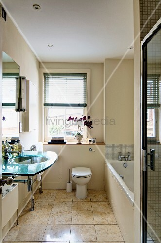 Glass washstand in narrow bathroom with floor tiles of polished marble