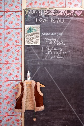 Notes on chalkboard door in kitchen with floral tiled wall
