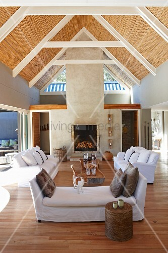 Open-plan interior with sofa set and exposed roof structure with ...
