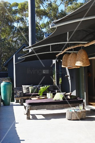 Rustic wooden benches with seat cushions on modern terrace below dark fabric awning with straw lampshades