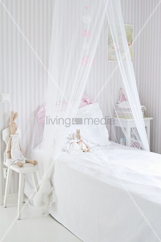 Bed with draped mosquito net and bunny soft toys leaning against pillow in child's bedroom