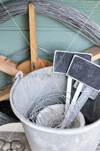 Plant labels in zinc bucket in front of wooden wheel wound in wire