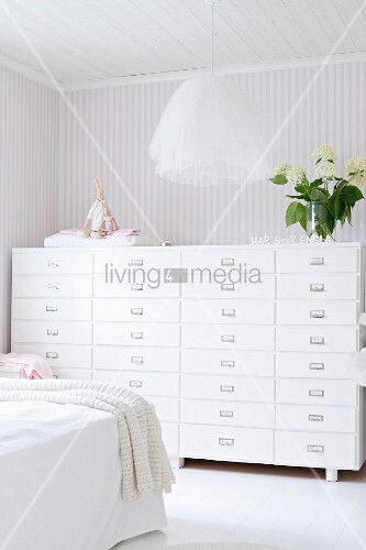 Pendant Lamp With Tulle Lampshade And Chest Of Drawers Against Pale Striped Wallpaper In Bedroom