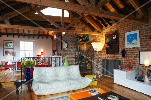 Open-plan interior with white sofa, contemporary sideboard, brick walls and exposed wooden roof joists