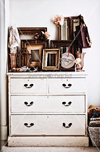 Many empty picture frames on white-painted vintage chest of drawers