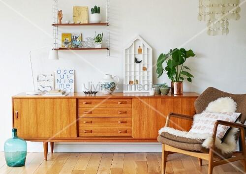 Fifties wooden sideboard and sheepskin rug on armchair