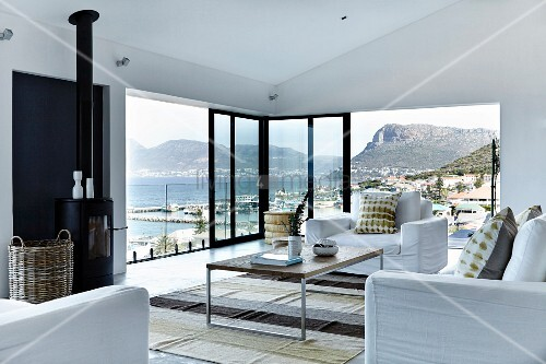 Elegant living room with white sofa set, delicate coffee table, partially glazed facade with sliding doors and panoramic view of mountainous coast