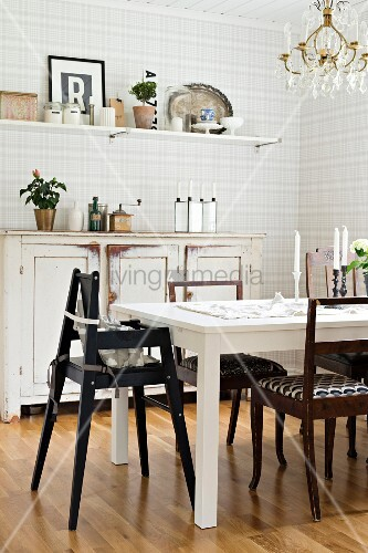 Black high chair at white table in front of vintage sideboard against grey ans white checked wallpaper