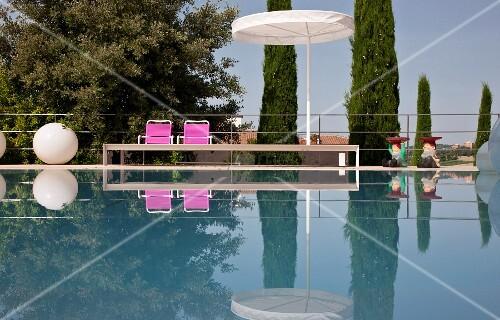 Eleganter Pool mit Sonnenschirm, pinkfarbenen Stühlen und kugelförmige Bodenlampe