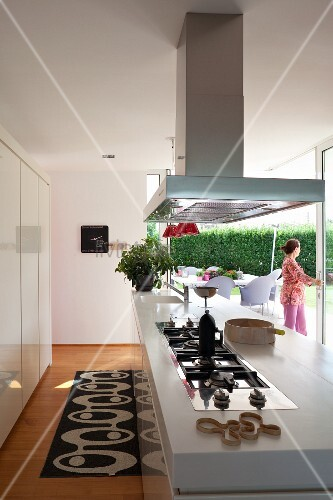 Kitchen counter with integrated gas hob below stainless steel extractor hood; woman standing in terrace windows in background
