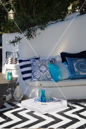 Patterned scatter cushions on white, masonry bench and black and white rug with geometric pattern