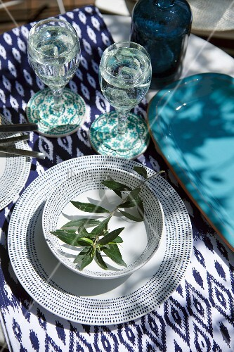 Place setting with blue and white patterned crockery, olive twig and ikat tablecloth
