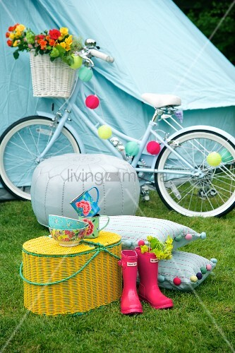 Pink Wellington boots next to yellow picnic basket in front of white pouffe and decorated bicycle in front of blue tent