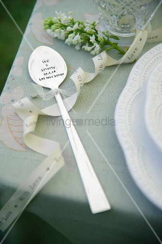 Ornamental spoon decorated with bow and sprig of white flowers on table