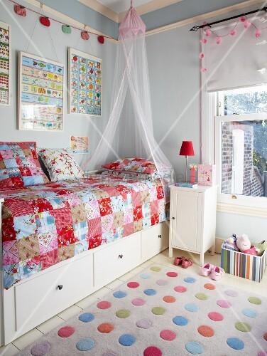 bunter punkte teppich vor bett mit schubladen und patchworkdecke in hellblau get ntem. Black Bedroom Furniture Sets. Home Design Ideas