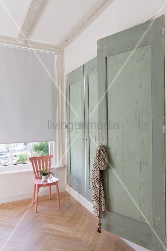Fitted wardrobes with green wooden doors and pink chair next to window