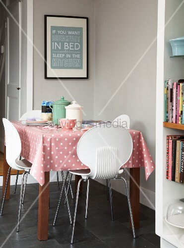 Dining area in corner of kitchen painted pale grey; white plastic chairs around table with pink tablecloth