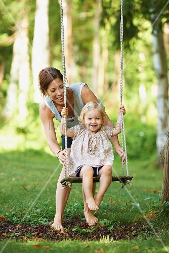 Mother with daughter on garden swing