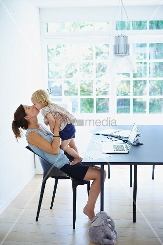 Mother cuddling and kissing daughter