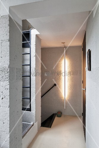 Breeze block walls; hallway with vertical strip light mounted on wall
