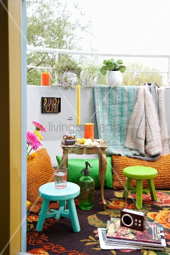 Rug, floor cushions, small Baroque table and brightly coloured stools on balcony
