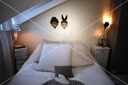 Bed below masks hung on wall flanked by lit table lamps on bedside tables in simple attic bedroom