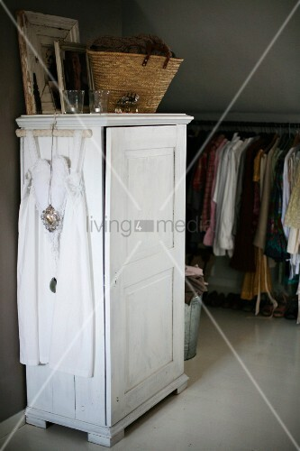 White dress on coat hanger hung on white-painted wardrobe with basket on top; clothes rail in background