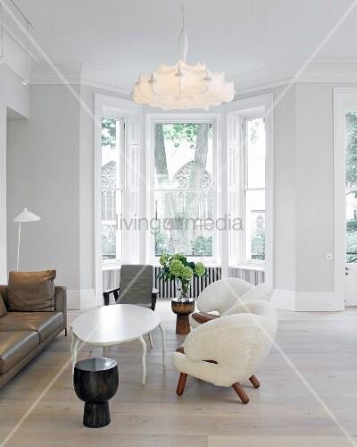 weisse extravagante sessel und ovaler tisch mit geschwungenen beinen unter pendelleuchte im. Black Bedroom Furniture Sets. Home Design Ideas