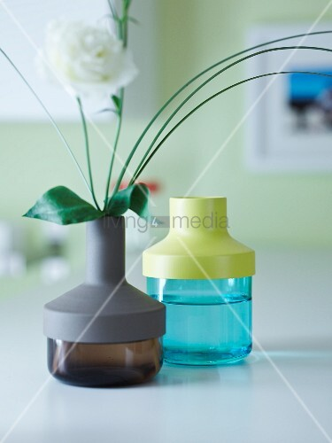 Coloured glass vases with different plastic lids