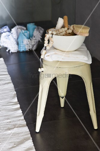 Shower utensils in bowl on Xavier Pauchard stool and dark grey floor tiles in bathroom