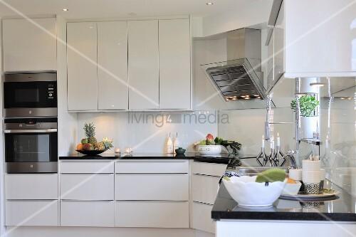 elegante k che mit weissen schr nken und schwarzer arbeitsplatte bild kaufen living4media. Black Bedroom Furniture Sets. Home Design Ideas