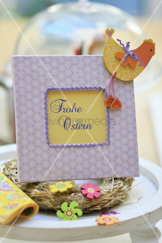 Hand-crafted picture frame with Easter greeting, straw wreath and ornaments