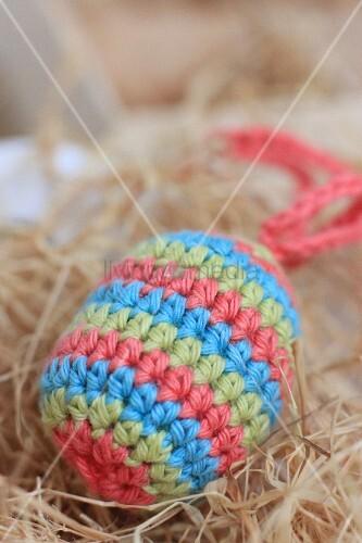 Striped, crocheted Easter egg amongst hay