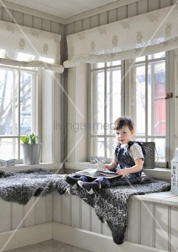 Kleiner Junge Auf Tierfell, In Holzverkleidetem Wintergarten Mit  Eingebauter Bank