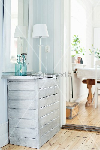 White table lamp on chest of drawers with pale varnish in corner of room next to open doorway