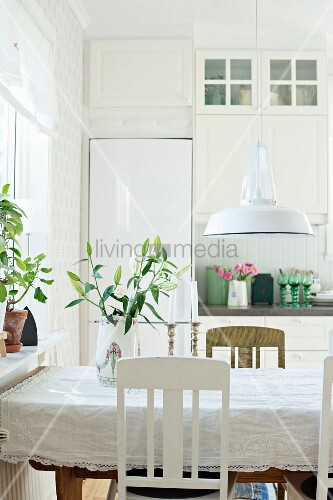 Detail of dining area; tablecloth on table below retro pendant lap with white, metal lampshade in rustic interior