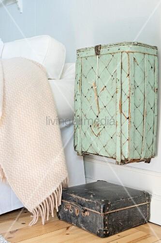 Alter Korb pastellgrün gestrichen, an Wand aufgehängt über Vintage Lederkoffer neben Bett