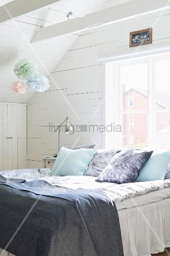kissen und decken auf bett vor fenster in holzverkleidetem. Black Bedroom Furniture Sets. Home Design Ideas