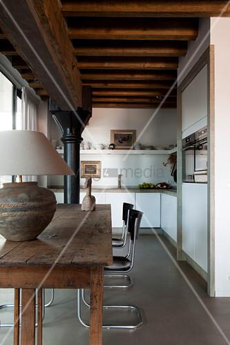 Tischleuchte auf rustikalem Holztisch und Klassiker Freischwinger in offener moderner Küche mit traditioneller Metallstütze