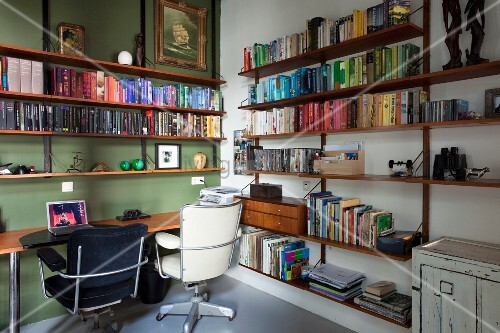 Black and white retro office chairs at desk in corner or room with green accent wall and bookcases