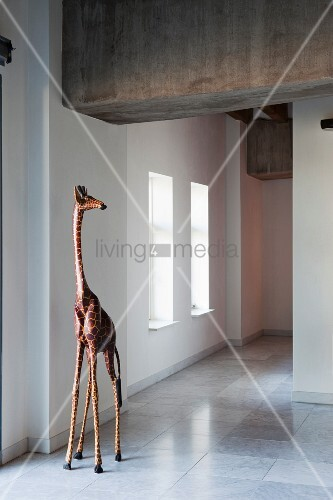 Giraffe sculpture on marble floor of modern, loft-style interior with industrial ambiance