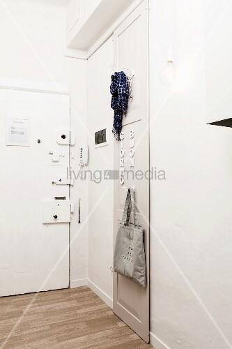 Heller Eingangsbereich mit mehrfach gesicherter Eingangstür und reduziertem Garderobenpaneel