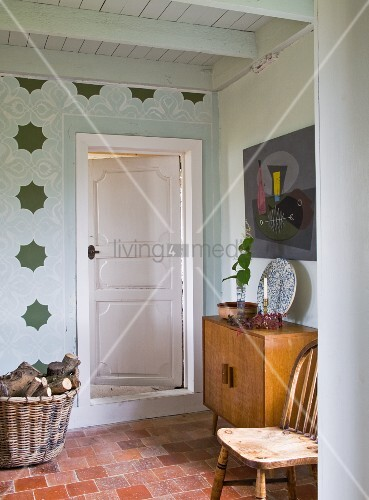 Basket of firewood next to interior door with chair and cabinet to one side on terracotta floor
