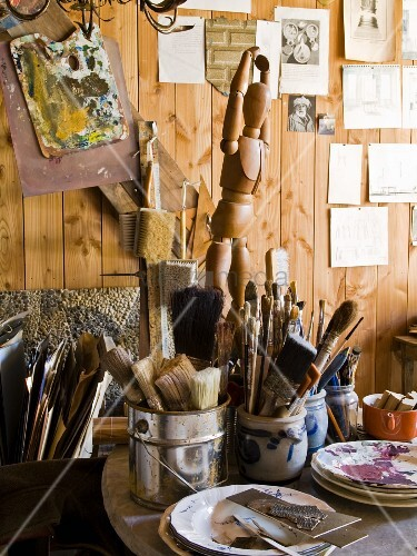 Painting utensils, beakers, various paintbrushes and wooden jointed mannequin in front of wooden wall in studio