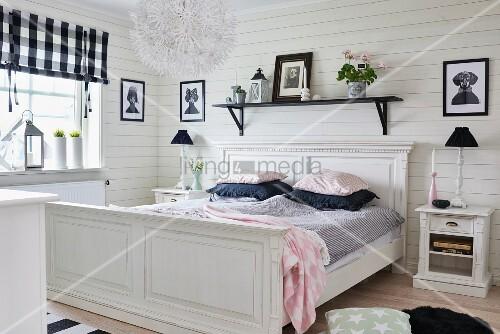 Weisses, Antikes Holzbett Vor Holzwand Mit Schwarzem Reagalbord,  Nachtkästchen Mit Tischlampen In Ländlichem Schlafzimmer