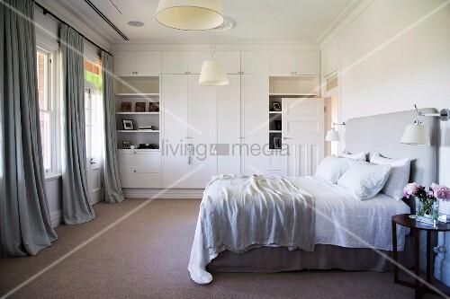 Helles Schlafzimmer in Grau und Weiss mit Einbauschrank und Doppelbett mit Kopfteil