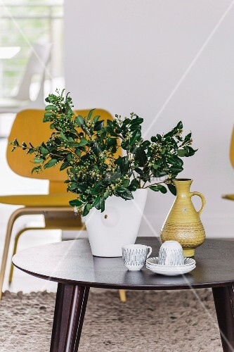 Crockery and vase of leaves on side table in front of classic chair